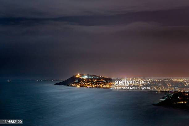 illuminated city by sea against sky at night - tunisia stock pictures, royalty-free photos & images