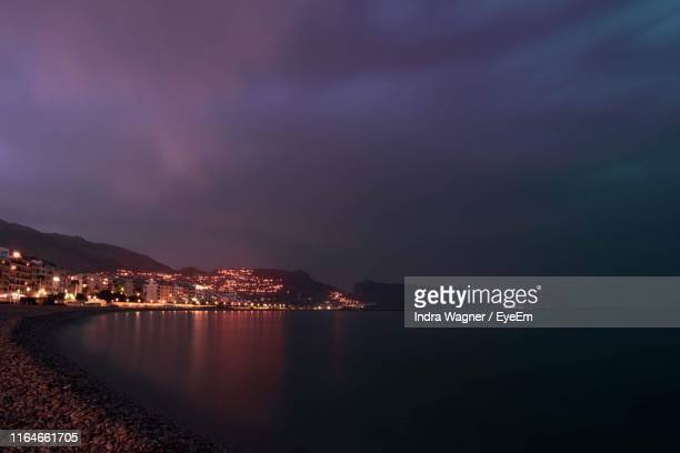 illuminated city by sea against sky at night - altea photos et images de collection