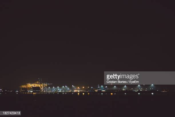 illuminated city by sea against sky at night - bortes stock pictures, royalty-free photos & images