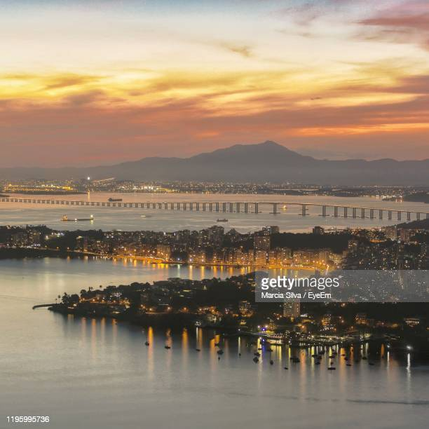 illuminated city by sea against sky during sunset - niteroi stock pictures, royalty-free photos & images