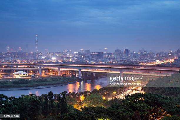 illuminated city lighting of downtown Taipei and Keelung river in blue hour, Taiwan