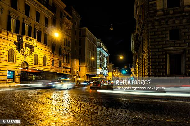 illuminated city road against at night - vgenopoulos stock pictures, royalty-free photos & images