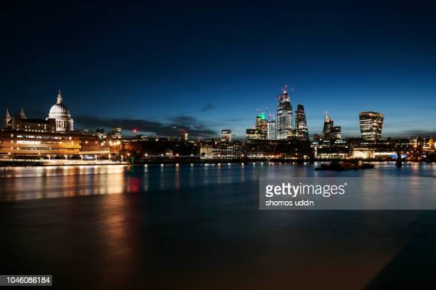 illuminated city skyline of london across thames river at twilight - skyline stock pictures, royalty-free photos & images