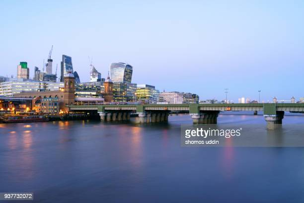 illuminated city skyline of london by waterfront at twilight - 2018 stock pictures, royalty-free photos & images
