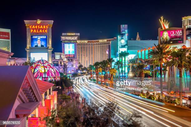 illuminated city street and buildings against sky at night - las vegas stock pictures, royalty-free photos & images