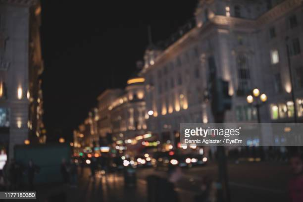 illuminated city street and buildings at night - focus on foreground stock pictures, royalty-free photos & images