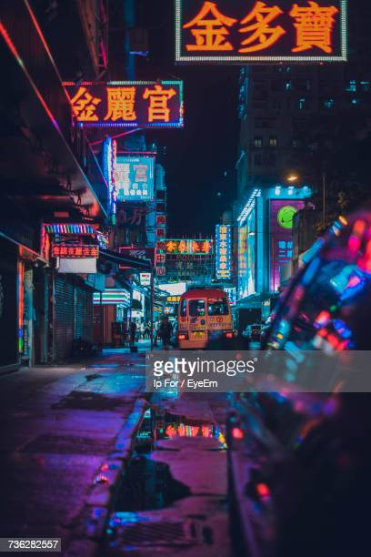illuminated city street at night - neon lighting stock pictures, royalty-free photos & images