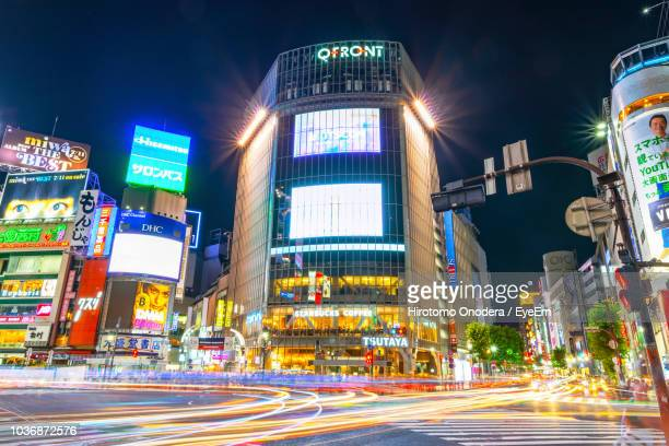 illuminated city street by buildings against sky at night - shibuya ward stock pictures, royalty-free photos & images