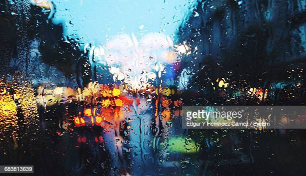 illuminated city street seen through wet car window at dusk - heavy rain stockfoto's en -beelden