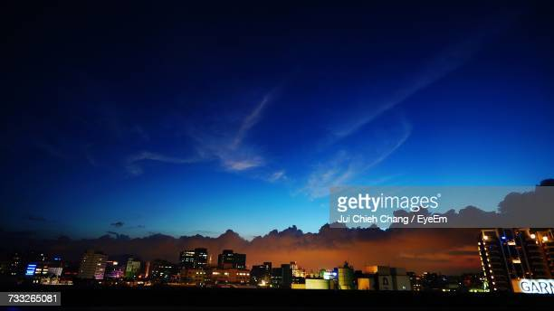 illuminated cityscape against blue sky at night - chang jui chieh stock photos and pictures