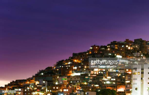 illuminated cityscape against clear sky at night - favela stock pictures, royalty-free photos & images