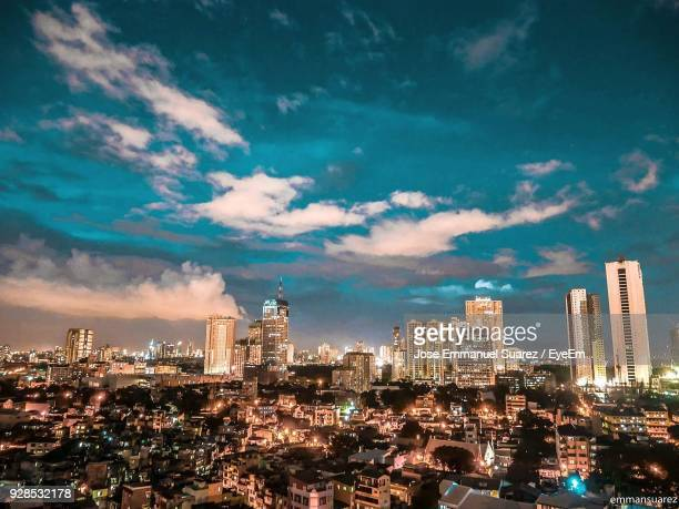 Illuminated Cityscape Against Cloudy Sky