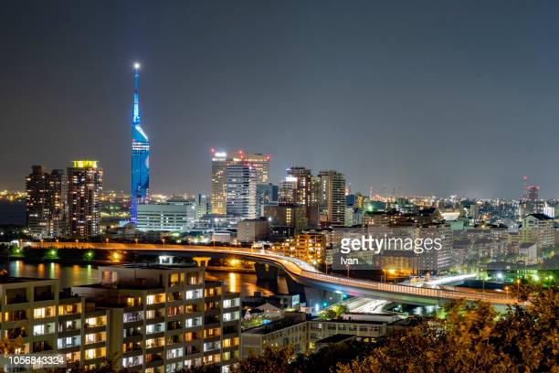 illuminated cityscape against sky at night - fukuoka city stock pictures, royalty-free photos & images