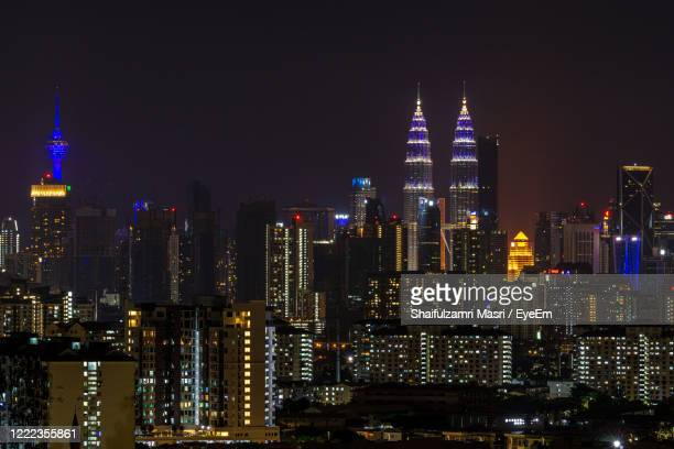 illuminated cityscape against sky at night - shaifulzamri stock-fotos und bilder