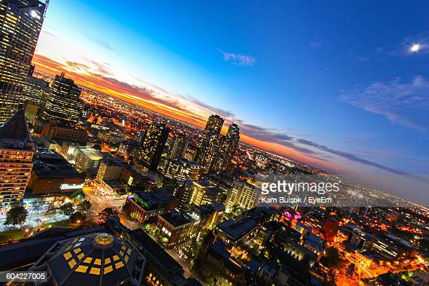 Illuminated Cityscape Against Sky During Sunset