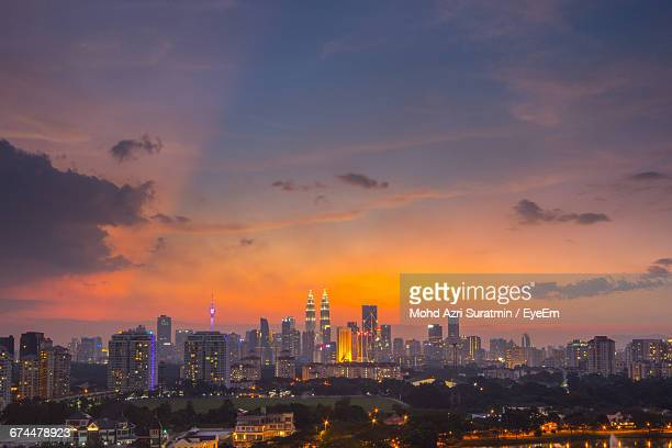 illuminated cityscape against sky during sunset - menara kuala lumpur tower stock photos and pictures