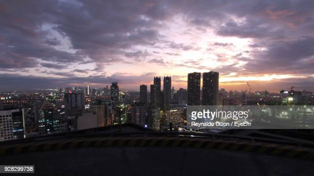 illuminated cityscape against sky during sunset - metro manila stock photos and pictures