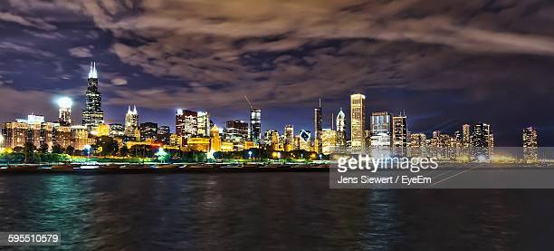 Illuminated Cityscape And Sea Against Sky