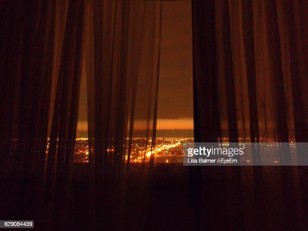 illuminated cityscape at night seen through curtains - translucent stock pictures, royalty-free photos & images