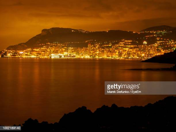 illuminated cityscape by sea against sky at night - marek stefunko stock pictures, royalty-free photos & images