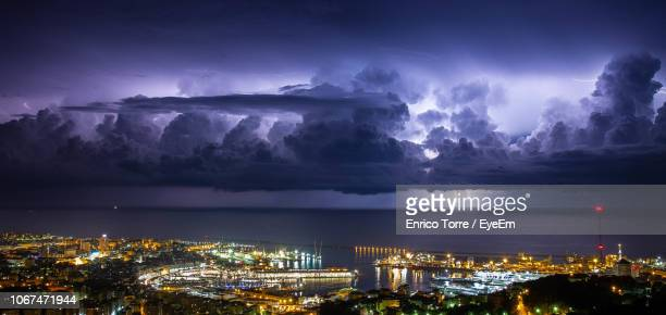 illuminated cityscape by sea against sky at night - genoa italy stock pictures, royalty-free photos & images