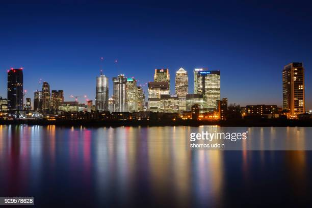 illuminated cityscape of east london skyline by waterfront at dusk - canary wharf stock photos and pictures