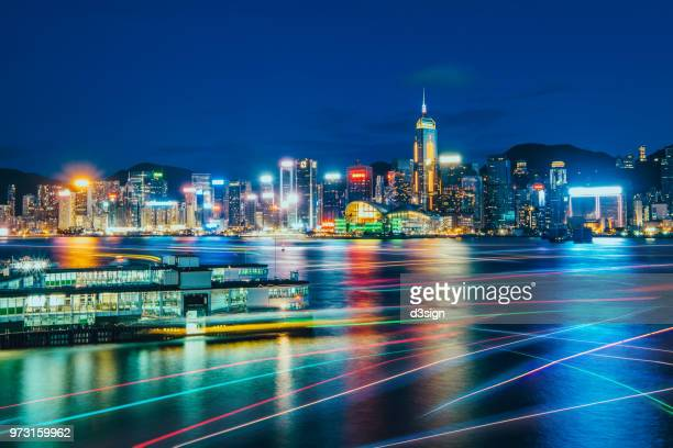 illuminated cityscape of hong kong at dusk and busy sea traffic with colourful light trails in victoria harbour - star ferry stock photos and pictures