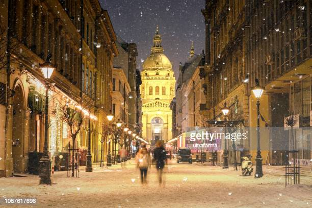 illuminated cityscape of zrinyi street in budapest with st stephen's basilica in a snowy winter landscape at dusk - europe stock pictures, royalty-free photos & images