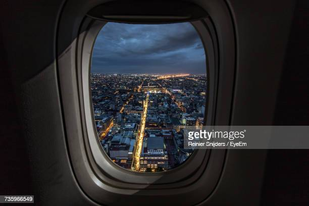 Illuminated Cityscape Seen Through Airplane Window At Night