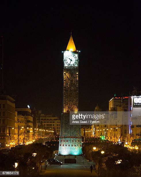 illuminated clock tower in city against clear sky at night - tunis stock pictures, royalty-free photos & images