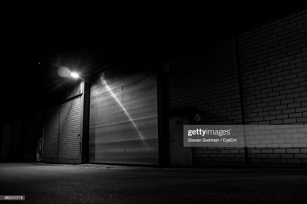 Illuminated closed shop by street at night stock photo getty images