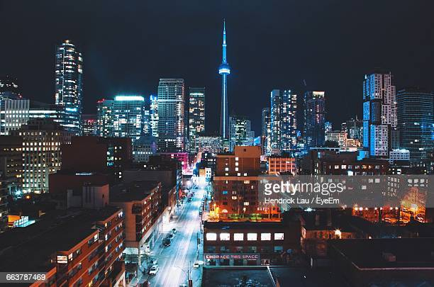 Illuminated Cn Tower Amidst Buildings At Night In City