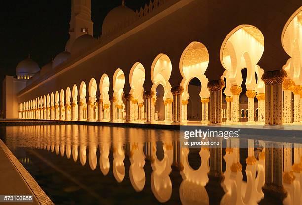 Illuminated colonnade reflecting in still pool