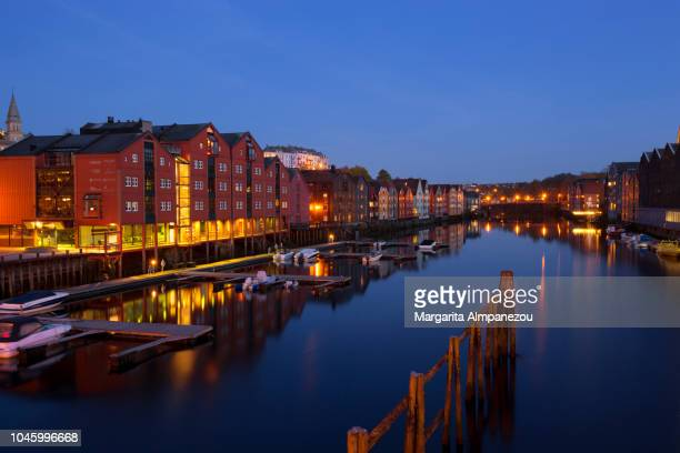 Illuminated colorful building across Nidelva River in Trondheim