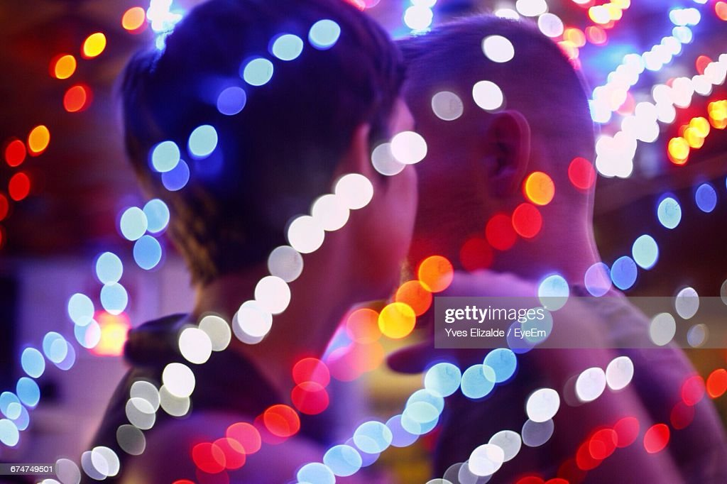 Illuminated Colorful Defocused Lights Against Man And Woman In Bar : Stock Photo