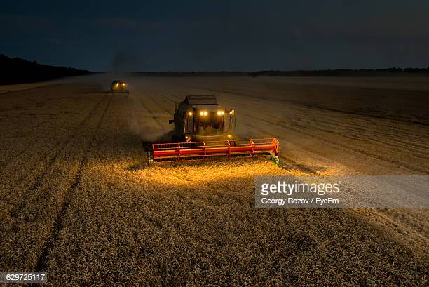 Illuminated Combine Harvester On Farm