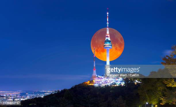 illuminated communications tower against blue sky at night - south korea stock pictures, royalty-free photos & images