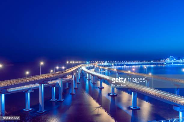 illuminated dalian cross-sea bridge at dusk - 中国北東部 ストックフォトと画像