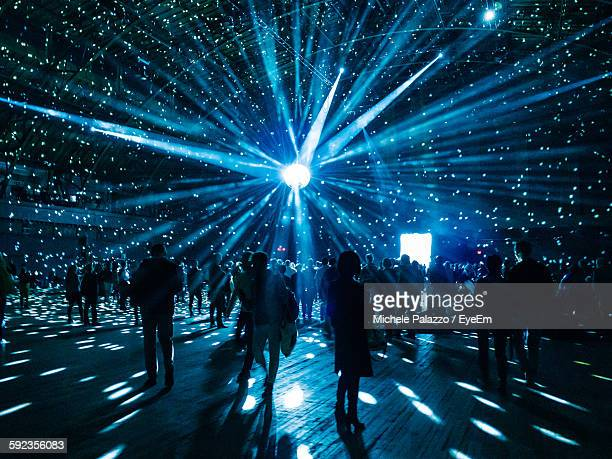 illuminated disco ball over silhouette people in nightclub - disco ball stock photos and pictures