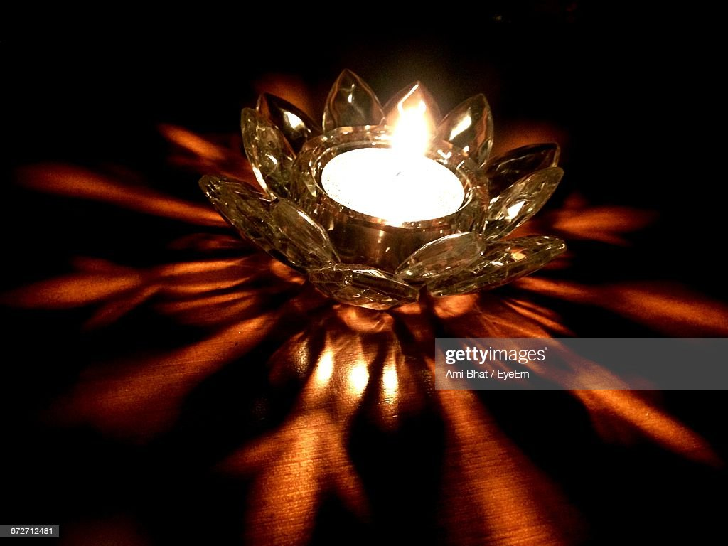 Illuminated Diya On Table In Darkroom : Stock Photo
