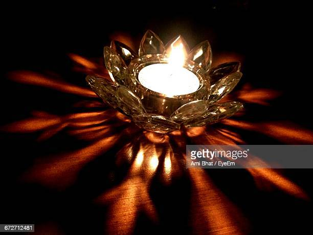 illuminated diya on table in darkroom - diya oil lamp stock pictures, royalty-free photos & images