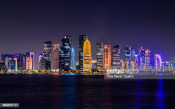 illuminated doha tower and skyscrapers by river in city against clear sky at night - doha stock photos and pictures
