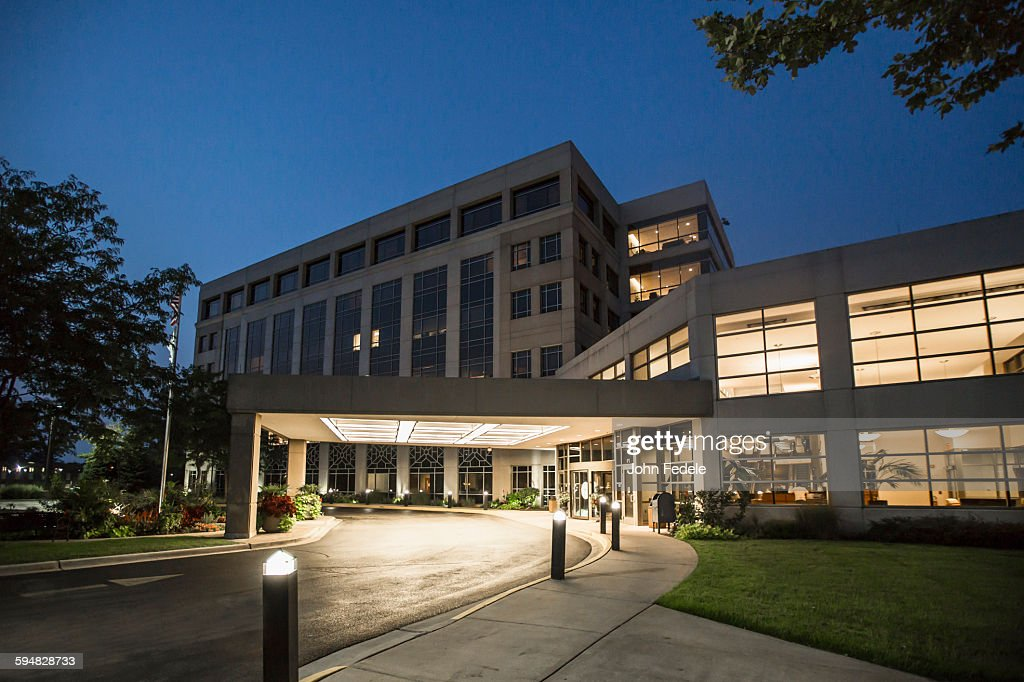 Illuminated driveway of hospital at night : Stock Photo
