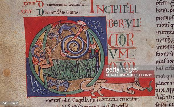 Illuminated drop cap depicting Satan transmitting a disease to Job miniature from Commentary on the Book of Job Cod B 41 Inf folio 84 verso 12th...