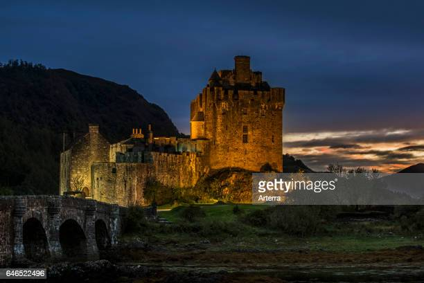 Illuminated Eilean Donan Castle at night in Loch Duich Ross and Cromarty Western Highlands of Scotland UK