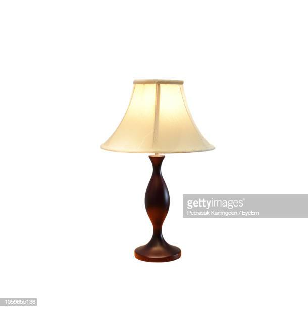 illuminated electric lamp against white background - lamp stock photos and pictures
