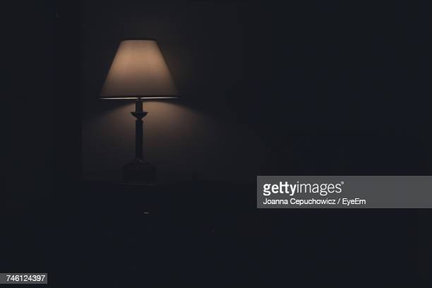 illuminated electric lamp by wall on table in darkroom at home - lamp stock photos and pictures