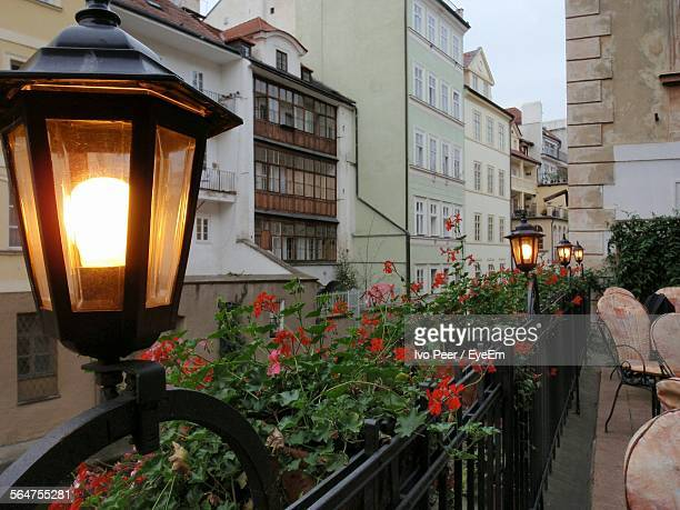 Illuminated Electric Lamp On Fence Outside Buildings