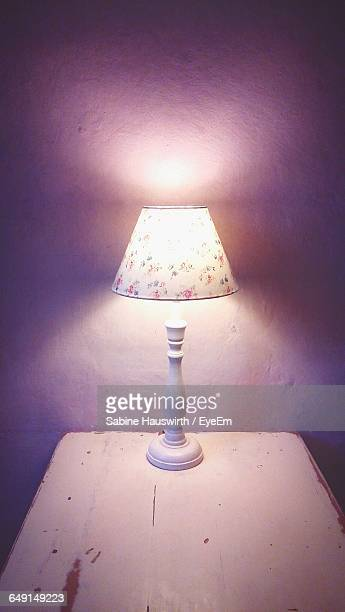 Illuminated Electric Lamp On Table Against Wall