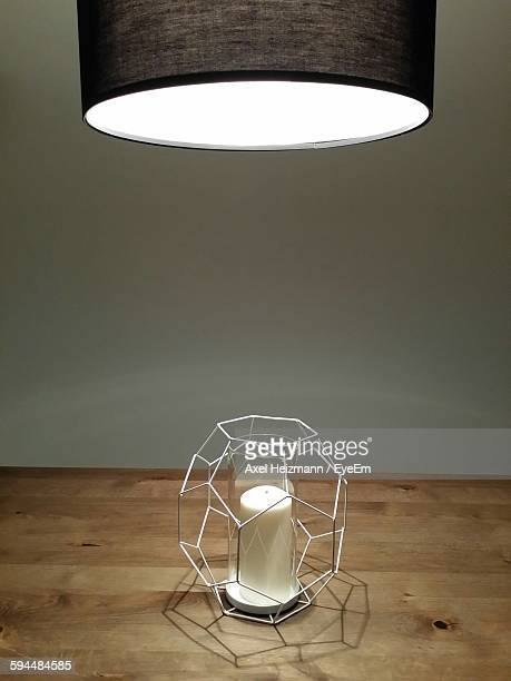 Illuminated Electric Light Over Candle On Wooden Table